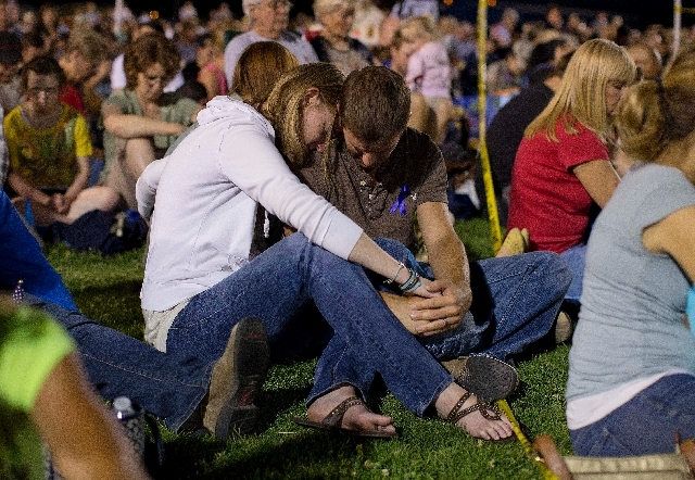 A couple bows their head in prayer during a candlelight vigil in Prescott, Ariz. on Tuesday, July 2 to honor the 19 Granite Mountain Hotshot firefighters who were killed by an out-of-control blaze ...