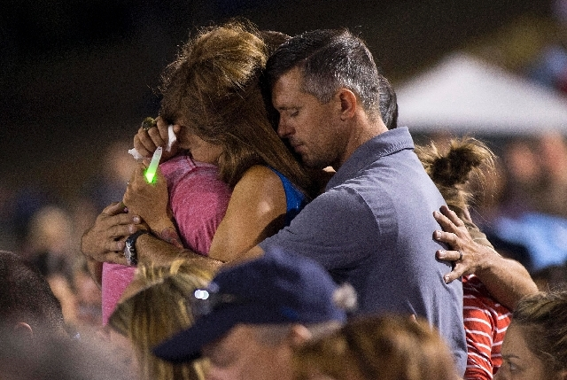 Juliann Ashcraft, left, wife of Granite Mountain Hotshot firefighter Andrew Ashcraft, hugs members of her family during a candlelight vigil, Tuesday, July 2 in Prescott, Ariz. Andrew Ashcraft was  ...