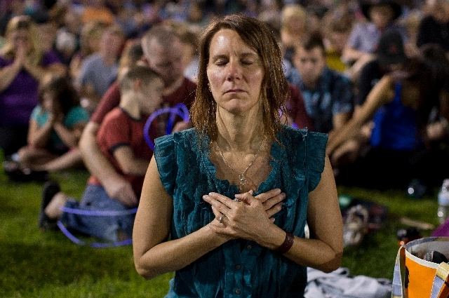 Leta Liberick closes her eyes in prayer during a candlelight vigil in Prescott, Ariz. on Tuesday, July 2 to honor the 19 Granite Mountain Hotshot firefighters who were killed by an out-of-control  ...
