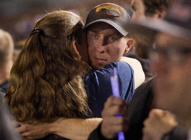 Firefighter Brendan McDonough embraces a mourner near the end of a candlelight vigil in Prescott, Ariz. on Tuesday, July 2. McDonough was the sole survivor of the 20-man Granite Mountain Hotshot C ...