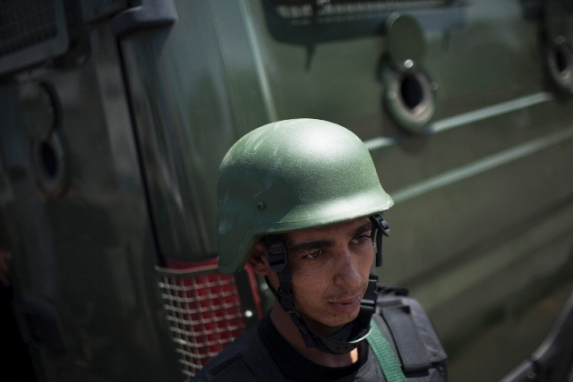 A member of Egyptian police special forces stands guard beside an armored vehicle, protecting a bridge between Tahrir Square and Cairo University, where Muslim Brotherhood supporters have gathered ...