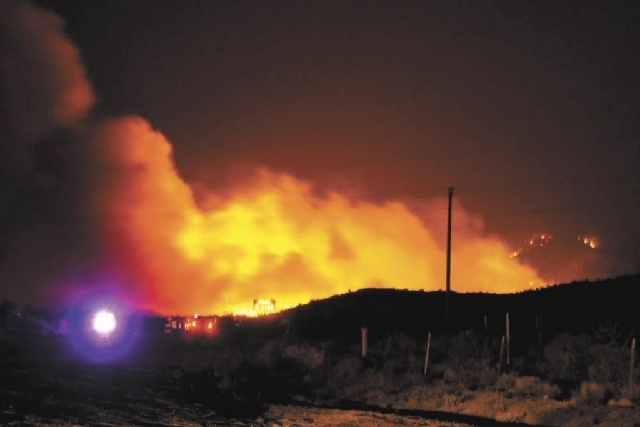 A wildfire burns Tuesday night near Dean Peak in the Hualapai Mountains in northwest Arizona. Residents of Pinion Pine, about 10 miles southeast of Kingman, were evacuated Tuesday night.