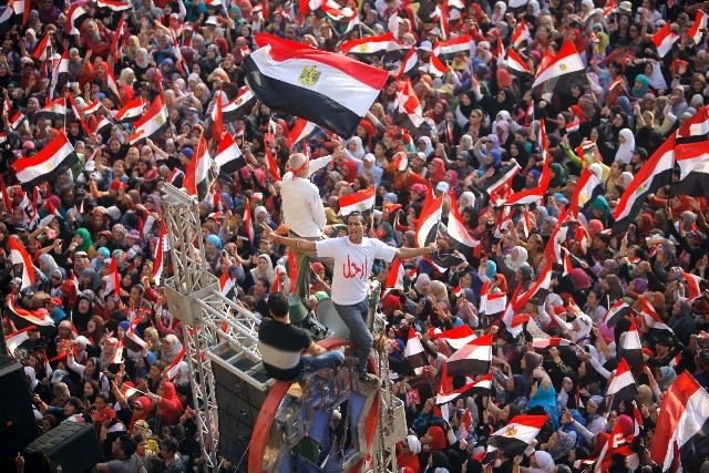 "Opponents  of Egypt's Islamist President Mohammed Morsi shout slogans and wave a national flags in Tahrir Square in Cairo, Egypt, Wednesday.  Arabic reads, "" leave."" The deadline on the military's ..."