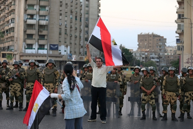 An Egyptian man holds a national flag as military special forces surround supporters of Islamist leader Mohammed Morsi in Nasser City, Cairo, Egypt, Wednesday. Army troops backed by armor and incl ...