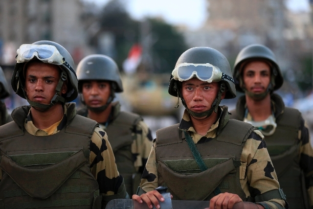 Military special forces surround supporters of Islamist leader Mohammed Morsi in Nasser City, Cairo, Egypt, Wednesday. Army troops backed by armor and including commandos have deployed across much ...