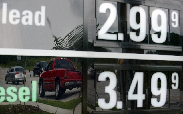 In this Monday, July 1 photo, vehicles are reflected in a sign advertising unleaded gas for $2.99 at a QuikTrip station in Greenville, S.C. Gasoline prices are on a summer slide, giving U.S. drive ...