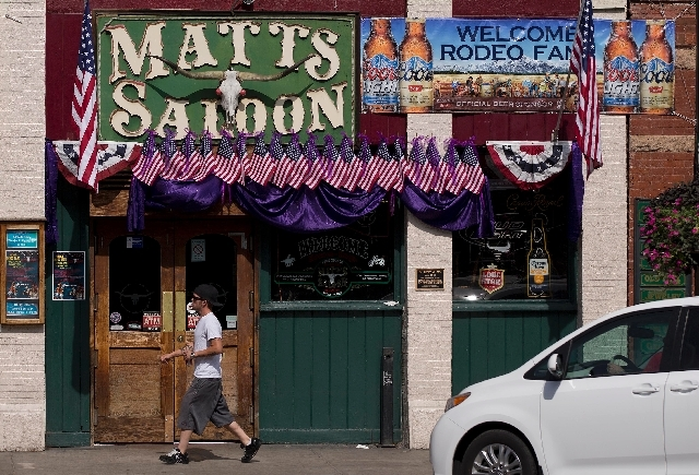 A man walks by a saloon decorated for the week's 4th of July and rodeo festivities, Wednesday in downtown Prescott, Arizona.  After 19 Granite Mountain Hotshot firefighters were killed in a blaze  ...