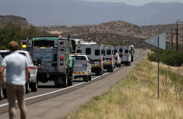 A procession of the vehicles left by the 19 elite Granite Mountain Hotshot crew members killed over the weekend are removed from the fire area near Yarnell Wednesday. Violent wind gusts on Sunday  ...