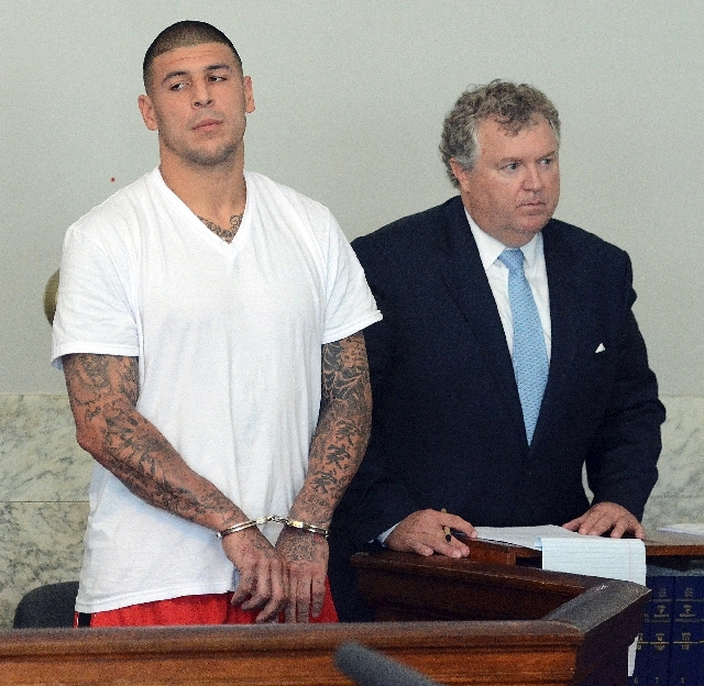 In this June 26 photo, former New England Patriots tight end Aaron Hernandez, left, stands with his attorney Michael Fee, right, during arraignment in Attleboro District Court in Attleboro, Mass.