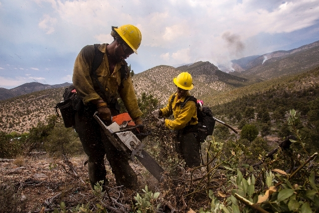 A Bear Divide hot shot crew called in from Santa Clarita, Calif., to help fight the Carpenter Canyon fire works to build a fire line around the Trout Canyon community on Wednesday. The fire has sc ...