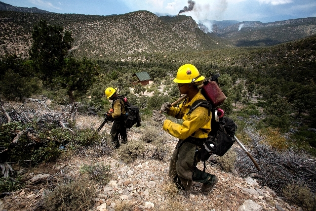 Members of a Bear Divide hot shot crew from Santa Clarita, Calif., build a fire line around the Trout Canyon community while the Carpenter Canyon fire burns in the background on Wednesday.