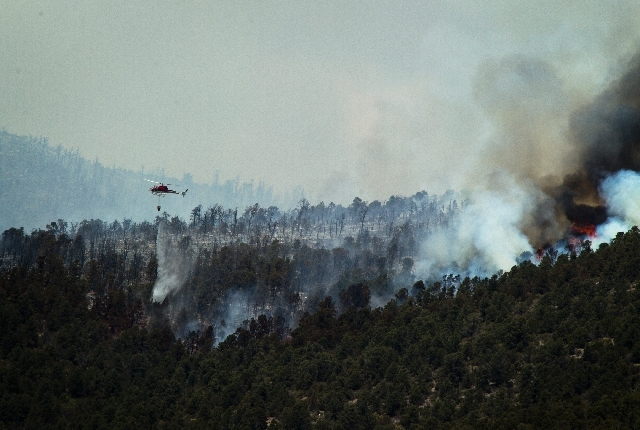 A helicopter makes a water drop on the Carpenter Canyon fire about two miles from the Trout Canyon community on Wednesday. About 120 firefighters are attacking the 1,950-acre fire.