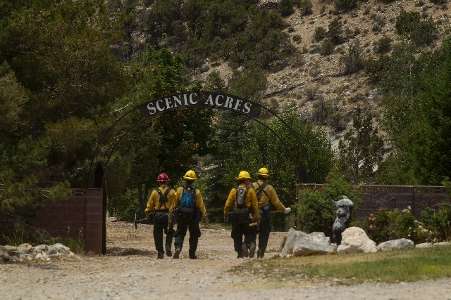 A fire crew walks in the Trout Canyon community while building a fire break on Wednesday. About 120 firefighters are attacking the 1,950 acre Carpenter Canyon fire.