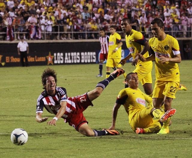 Chivas' Carlos Fierro (21) gets taken out by Club America's Jonathan Sanchez at Sam Boyd Stadium in Las Vegas on Wednesday.