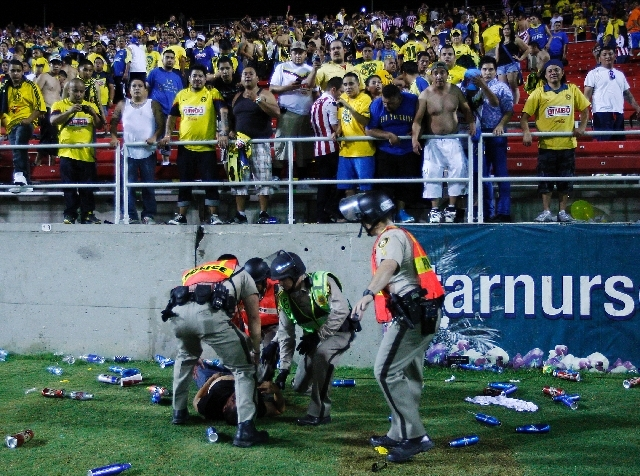 Police attend to a fan who got beaten up at Sam Boyd Stadium after the Chivas vs. Club America game in Las Vegas on Wednesday.