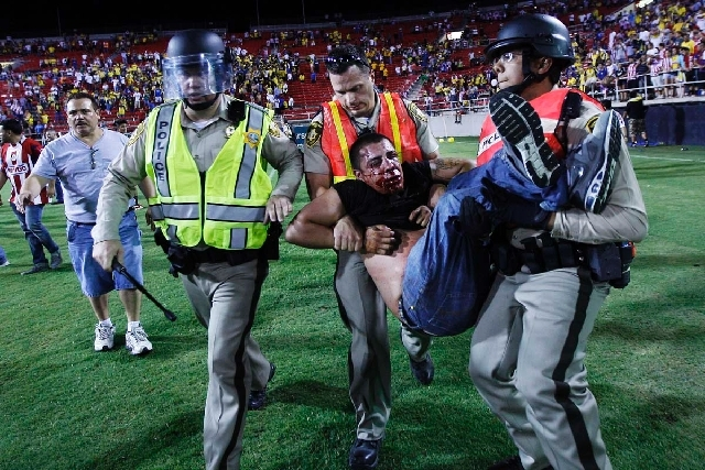 A bloody and beaten soccer fan is carried out of Sam Boyd Stadium after El Super Clasico in Las Vegas Wednesday night.