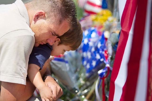 Duane Oliver of Prescott Valley hugs his son, Conner Oliver, 2, by a memorial for the fallen firefighters in front of Prescott Fire Station #7 on Monday. Nineteen firefighters have died in the Yar ...