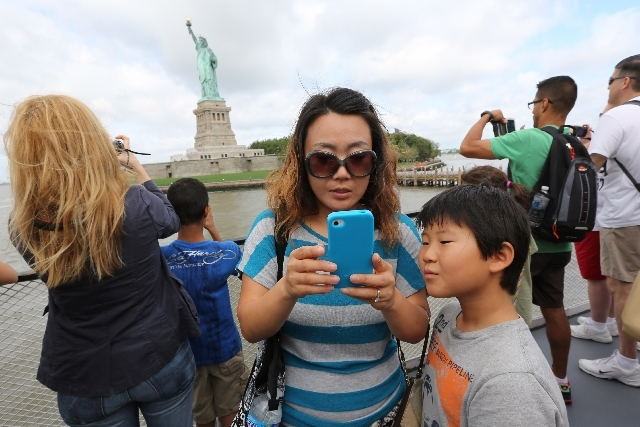 Visitors to fhe Statue of Liberty take photos as they arrive on the first tourist ferry to leave Manhattan, Thursday in New York. The Statue of Liberty finally reopened on the Fourth of July month ...