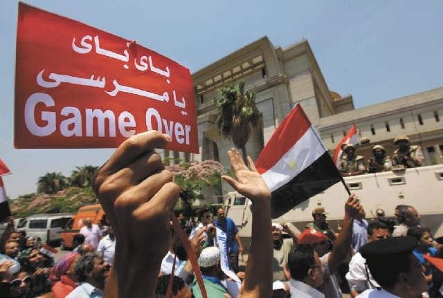 "Egyptians celebrate in front of the constitutional court after Egypt's chief justice Adly Mansour was sworn in as the nation's interim president Thursday. Arabic reads, "" bye bye Morsi."" The chief ..."