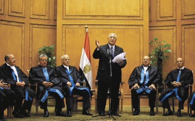 Egypt's chief justice Adly Mansour, center, speaks at his swearing in ceremony as nation's interim president Thursday. The chief justice of Egypt's Supreme Constitutional Court was sworn in Thursd ...
