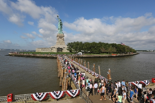 Visitors to the Statue of Liberty disembark onto Liberty Island from the first ferry to leave Manhattan, Thursday in New York. The Statue of Liberty finally reopened on the Fourth of July months a ...