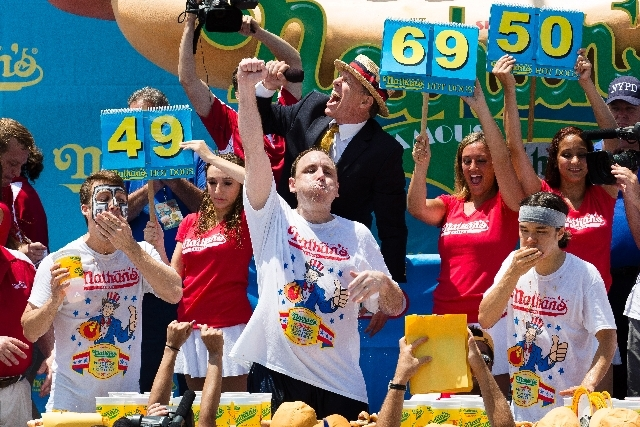 Joey Chestnut, center, wins the Nathan's Famous Fourth of July International Hot Dog Eating Contest Thursday with a total of 69 hot dogs and buns, alongside Tim Janus, left, and Matt Stonie, right ...