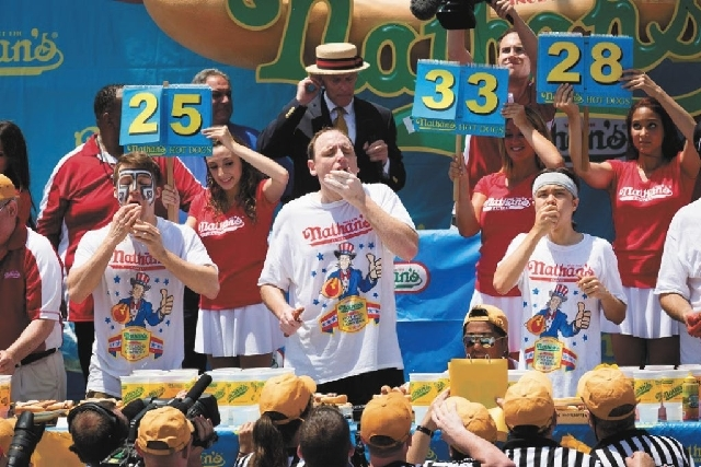 Tim Janus, left, Joey Chestnut, and Matt Stonie compete in the Nathan's Famous Fourth of July International Hot Dog Eating contest at Coney Island on Thursday.