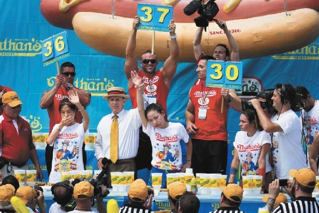 Sonya Thomas, center, wins the Nathan's Famous Fourth of July International Hot Dog Eating contest Thursday alongside Juliet Lee, left, and Michelle Lesco, right, at Coney Island.