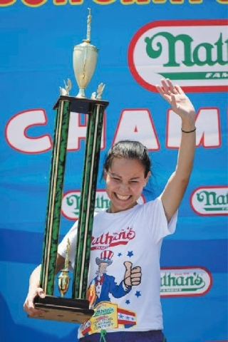Sonya Thomas holds the first place trophy Thursday after winning the Nathan's Famous Fourth of July International Hot Dog Eating contest with a total of 36 3/4 hot dogs and buns at Coney Island.
