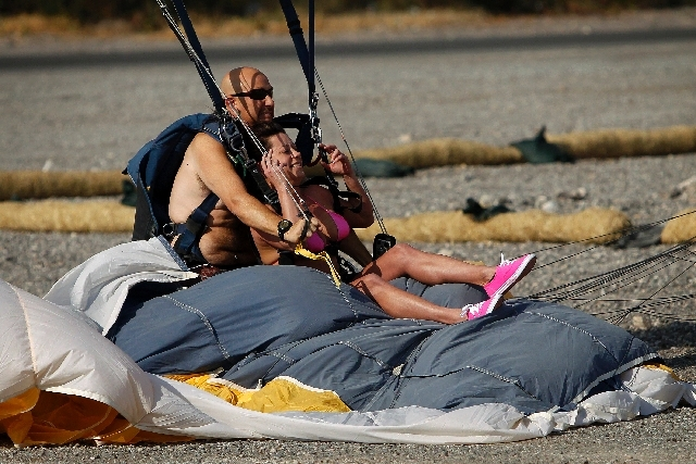 Melissa Dandron, right, lands into another parachute with Jim Dolan during a charity event Thursday at Larry Flynt's Hustler Club.