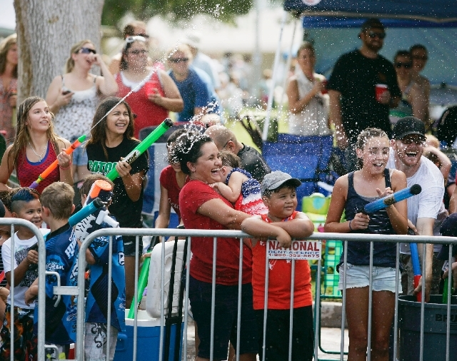 Parade watchers get sprayed with water Thursday. Temperatures were in the 100s during the parade in Boulder City.