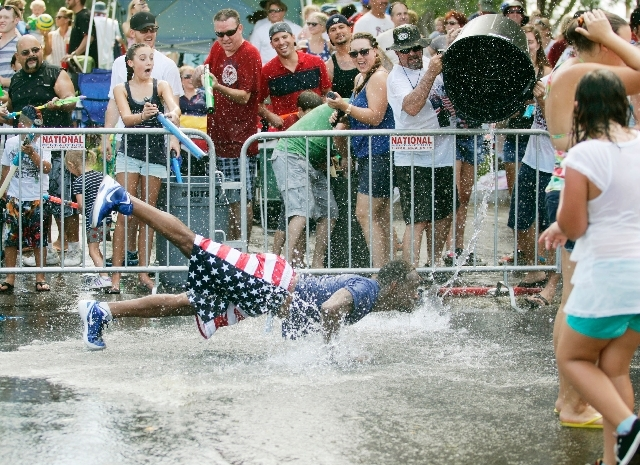 Roger Johnson is doused with water as he does pushups for the crowd during the 65th annual Boulder City Damboree Celebration parade Thursday on Avenue B . A section of the parade was set aside for ...