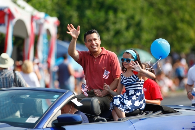Nevada Gov. Brian Sandoval waves to the crowd during the 19th Annual Summerlin Council Patriotic Parade on Thursday.