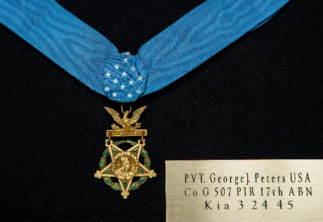 "Attached to a  neck ribbon with 13 white stars, Pvt. George J. Peters' World War II Medal of Honor hangs from a ""Valor"" bar Tuesday at American Legion Post 8. The five-point gold star Army medal i ..."