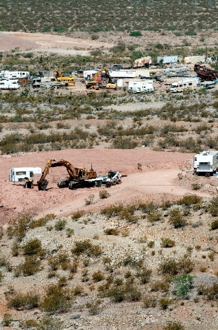 Construction trucks and equipment sit at Quartette mine, Wednesday near Searchlight, Nev.