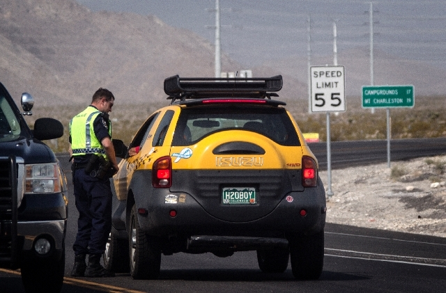 A Nevada Highway Patrol officer stops a Kyle Canyon resident at State Route 157 and U.S. Highway 95 on July 5. More residents will be allowed to return to their mountain homes near Las Vegas as fi ...