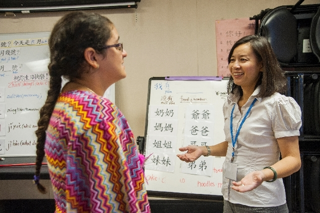 Chinese language instructor Chi Chen helps Abril Ramos, 11, with pronunciation during a Mandarin Chinese language and culture class at the Winchester Cultural Center.