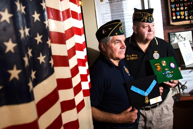Commander Rod Carlone, left, holds Army Pvt. George J. Peters' Medal of Honor while past commander Jerry Autrey holds a display of Peters' patches and awards Tuesday at American Legion Post 8.