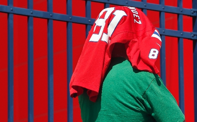 A Patriots fan protects his head from the sun while waiting to exchange his Aaron Hernandez jersey at Gillette Stadium in Foxborough, Mass., on Saturday.