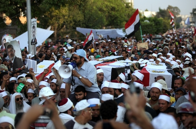 Supporters of Egypt's ousted President Mohammed Morsi carry coffins, covered with the national flag, of four men killed after Egyptian troops opened fire on mostly Islamist protesters marching on  ...
