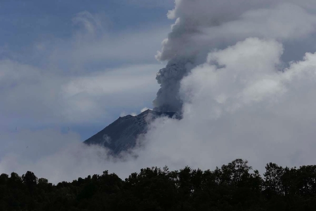 A plume of ash and steam rises from the Popocatepetl volcano during a brief view from cloud cover as seen from the town of Santiago Xalizintla, Mexico, Saturday. Just east of Mexico City, the volc ...