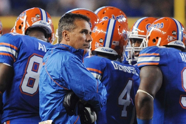 """Florida coach Urban Meyer glances at the scoreboard during a 2010 game against South Carolina in Gainesville, Fla. Meyer, now caoch at Ohio State, said it is """"wrong and irresponsible"""" to connect h ..."""