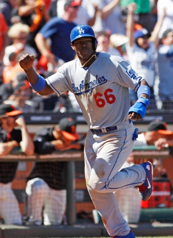 Los Angeles Dodgers' Yasiel Puig scores on an A.J. Ellis double against the San Francisco Giants during the ninth inning of a baseball game in San Francisco, Sunday, July 7.