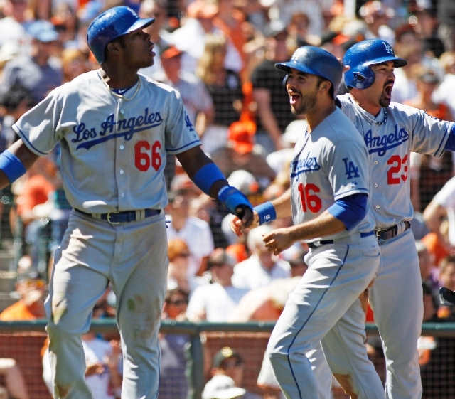 Los Angeles Dodgers' Yasiel Puig, left, Andre Ethier, center, and Adrian Gonzalez react after scoring against the San Francisco Giants during the ninth inning of a baseball game in San Francisco,  ...