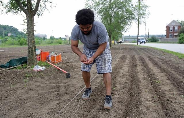 Volunteer Jonathan Sears plants seeds in a garden along Spring Grove Avenue near Mill Creek in Cincinnati.