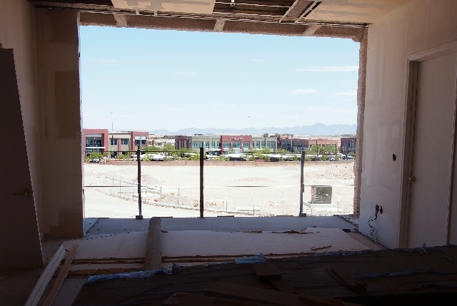 A view out the floor-to-ceiling window on a ground floor apartment overlooks development next to Clark County 215. Construction is set to begin again on the newly named The Gramercy development on ...