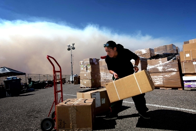 Indiara Modesto works outside in the supply unit area at Centennial High School, the Carpenter One fire command center, in Las Vegas on Monday. The wildfire, which encompasses more than 19,000 acr ...