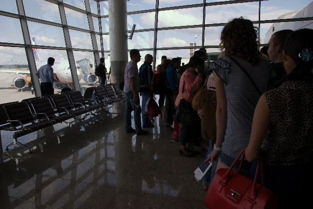 Passangers queue for boarding as the Aeroflot flight to Havana plane is seen parked next to a gate of Sheremetyevo airport outside Moscow, Russia, on Tuesday. NSA leaker Edward Snowden is believed ...