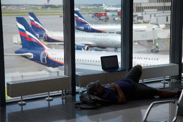 A passenger rests in Sheremetyevo airport outside Moscow, Russia, on Tuesday. NSA leaker Edward Snowden is believed to be stuck in the transit zone of Moscow's Sheremetyevo airport since his arriv ...