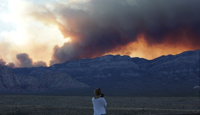 A young woman takes a picture of the Carpenter 1 fire near Las Vegas on Monday.